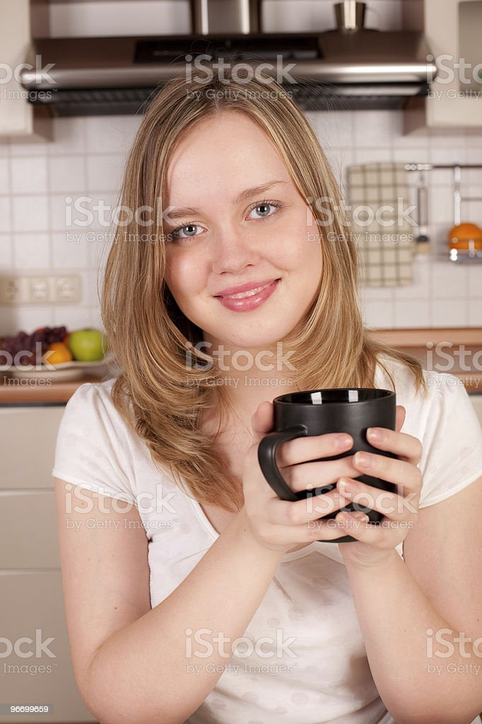 Happy woman with a cup of coffee in her hands royalty-free stock photo
