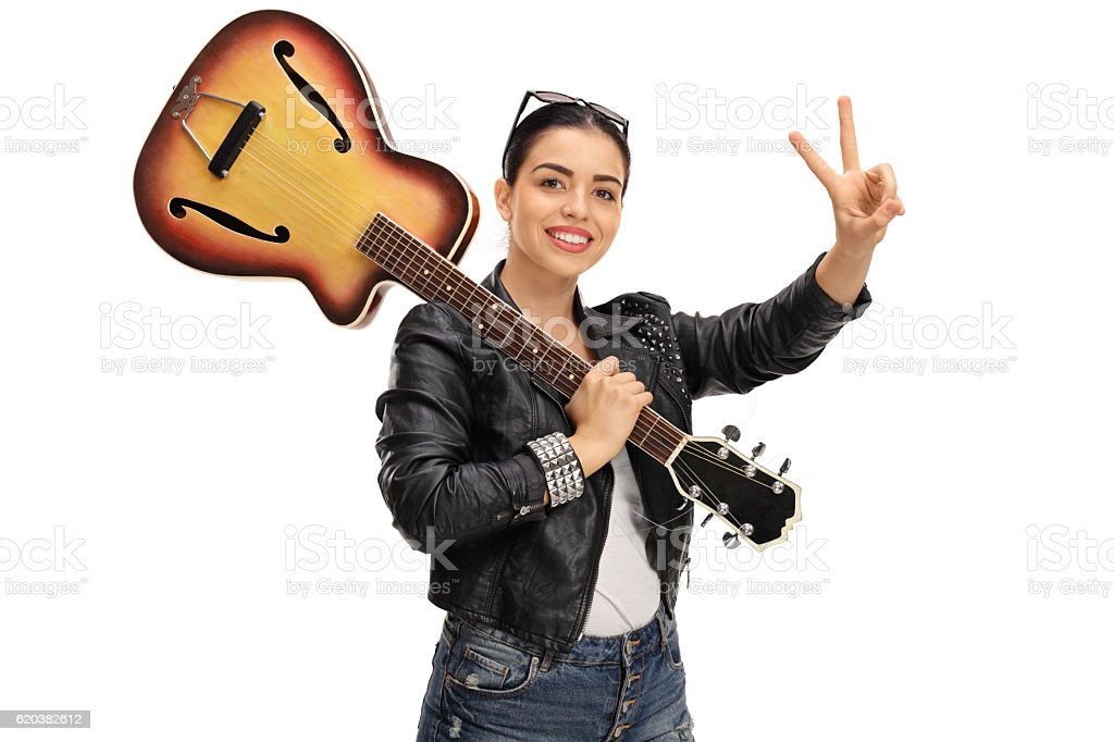 Happy woman with a guitar making a peace sign stock photo