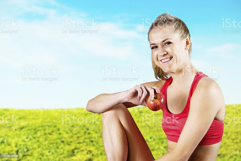 Happy woman with an apple in a field royalty-free stock photo