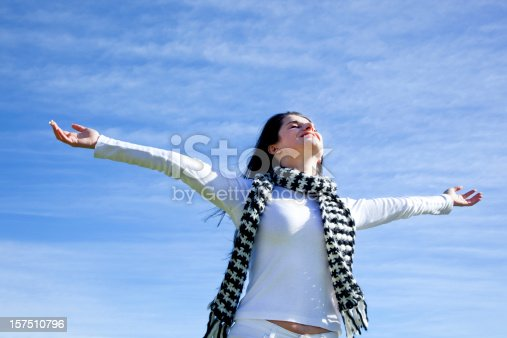 ecstatic woman with arms outstretched with sky and clouds in the background