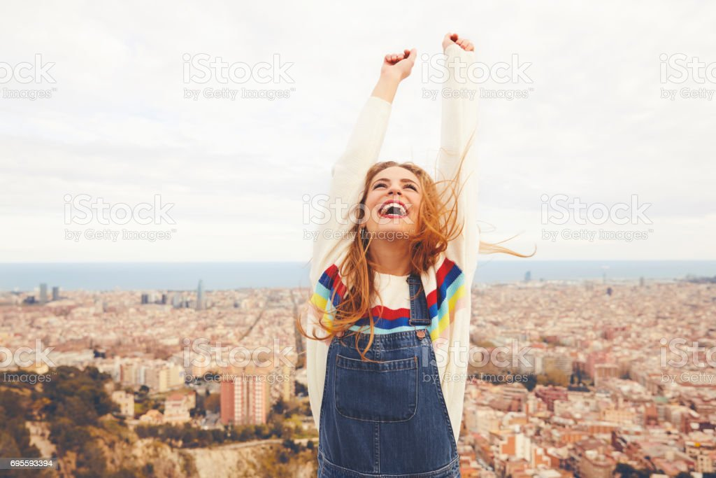 Happy woman with arms raised against cityscape stock photo