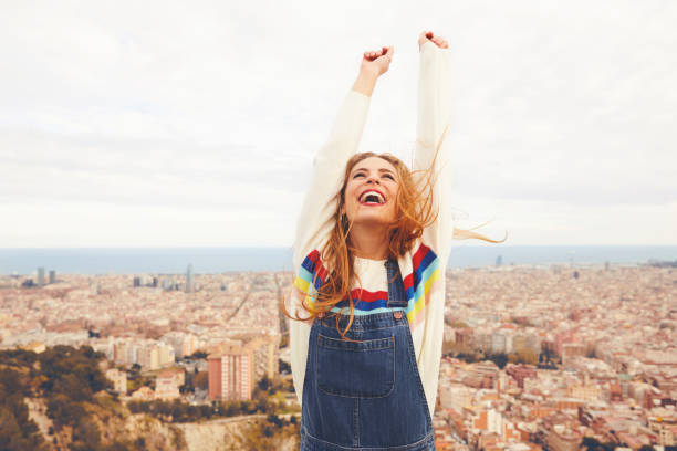 Happy woman with arms raised against cityscape - foto stock