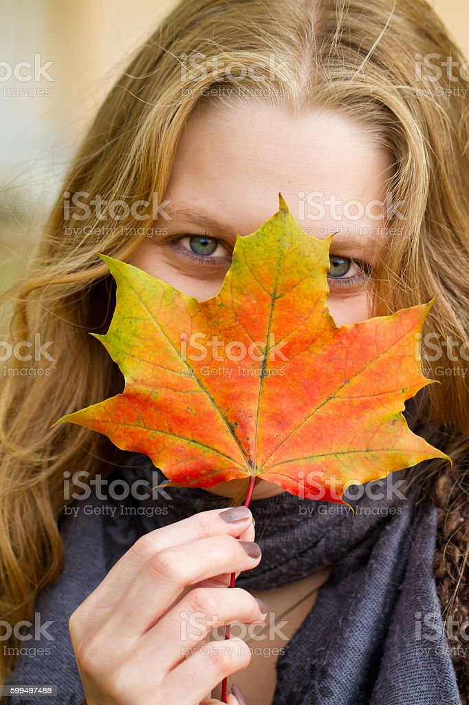 Happy woman with autumn leaves stock photo