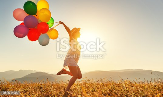 young happy woman with balloons at sunset in summer
