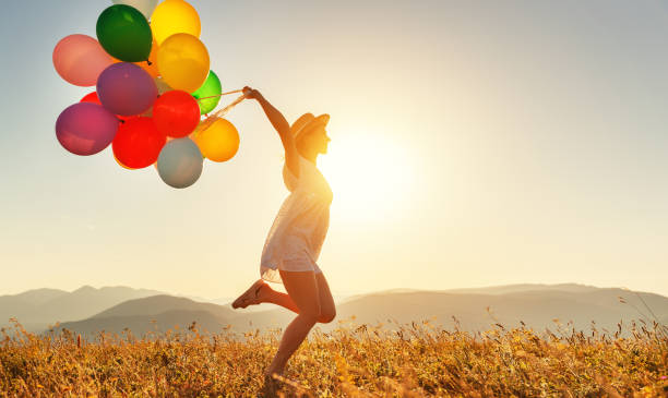 happy woman with balloons at sunset in summer - mulher balões imagens e fotografias de stock