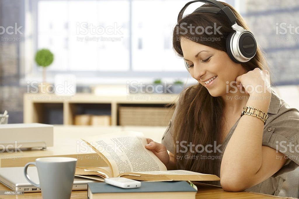 Happy woman with book and headphones stock photo