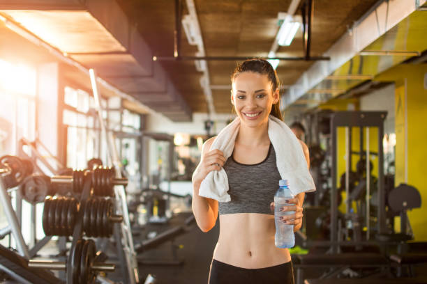 Happy woman with bottle of water and towel at gym stock photo