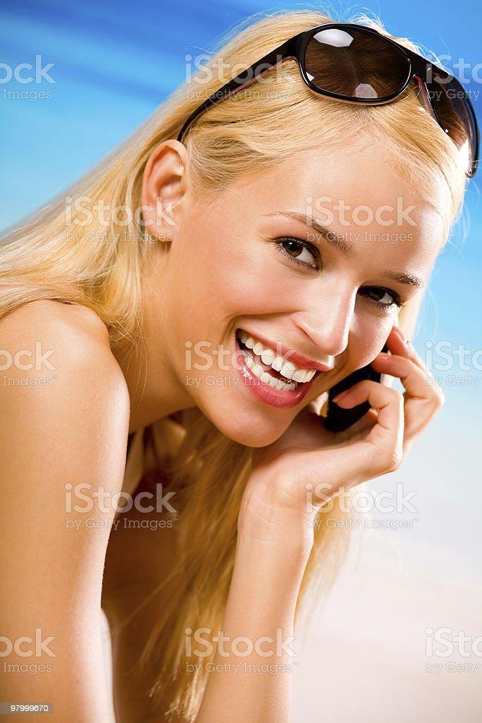 Mulher feliz com celular na praia foto royalty-free