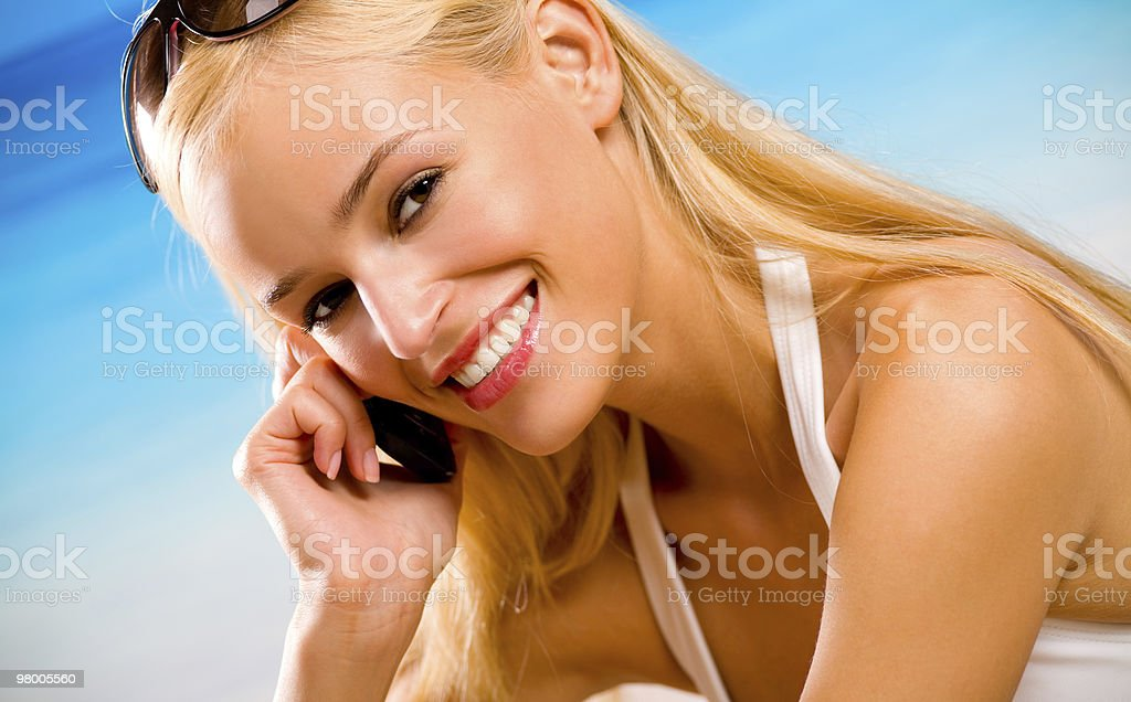 Happy woman with cell phone on beach royalty free stockfoto
