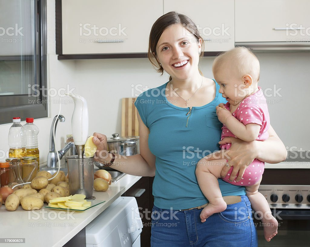 Happy woman with child  cooking mashed potatoes stock photo