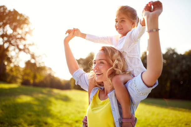 happy woman with child together outdoor - family health stock photos and pictures
