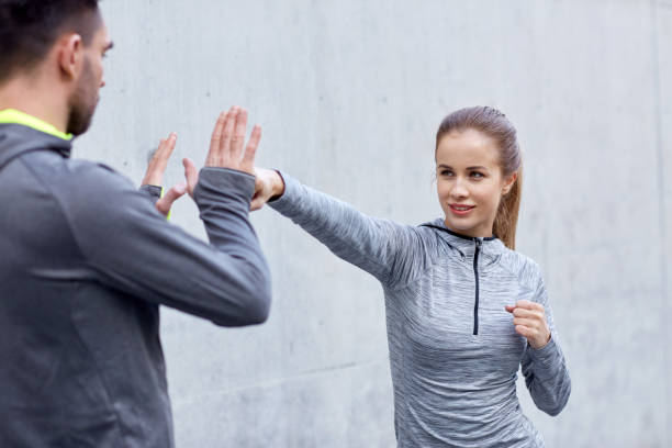 happy woman with coach working out strike outdoors fitness, sport, martial arts, self-defense and people concept - happy woman with personal trainer working out strike outdoors self defense stock pictures, royalty-free photos & images