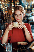 Portrait of smiling happy elegant woman drinking cup of coffee at table in outdoor cafe