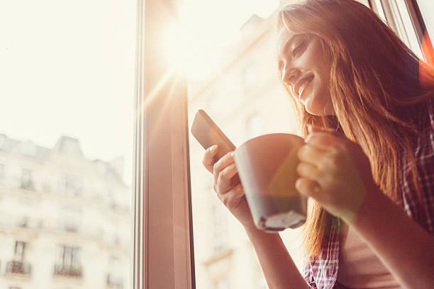 femme heureuse avec la tasse de café, envoyer des sms sur la fenêtre ouverte - europe centrale photos et images de collection