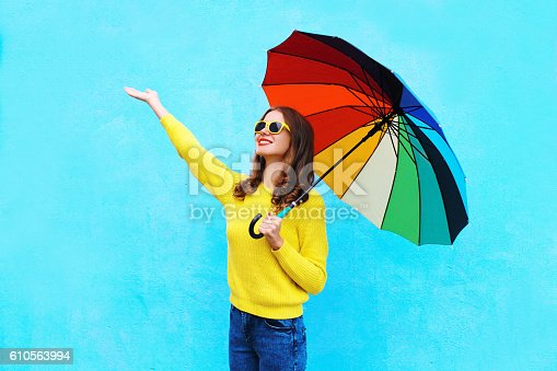 istock Happy woman with colorful umbrella in autumn over blue background 610563994