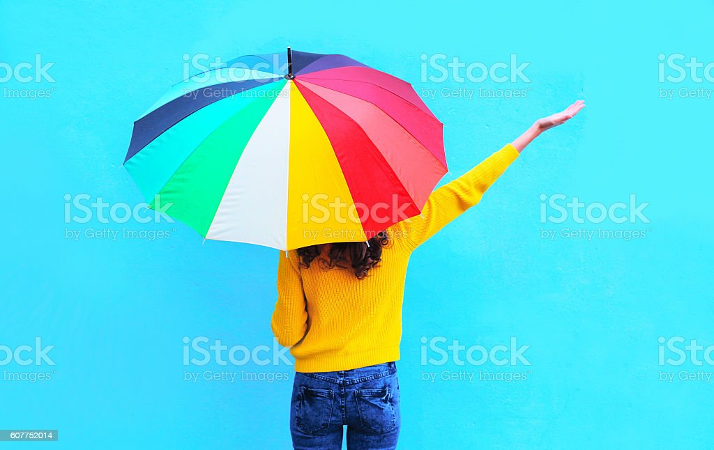 Happy woman with colorful umbrella raised hands up autumn stock photo