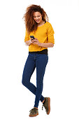 istock happy woman with curly hair standing against isolated white background with mobile phone 1035693110