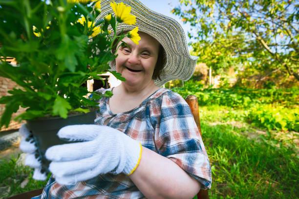 Glückliche Frau mit Down-Syndrom bereit, Blumen zu pflanzen. gartenarbeit. – Foto