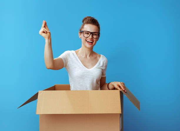 happy woman with fingers snapping in cardboard box on blue happy modern woman in white t-shirt with fingers snapping in a cardboard box isolated on blue background snapping stock pictures, royalty-free photos & images
