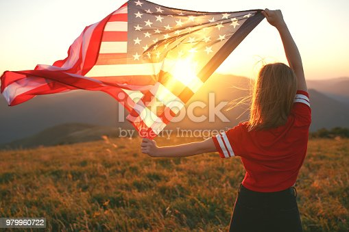 istock happy woman with flag of united states enjoying the sunset on nature 979960722