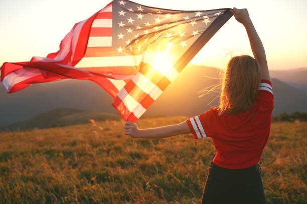 happy woman with flag of united states enjoying the sunset on nature - happy 4th of july zdjęcia i obrazy z banku zdjęć