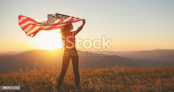 istock happy woman with flag of united states enjoying the sunset on nature 982914232