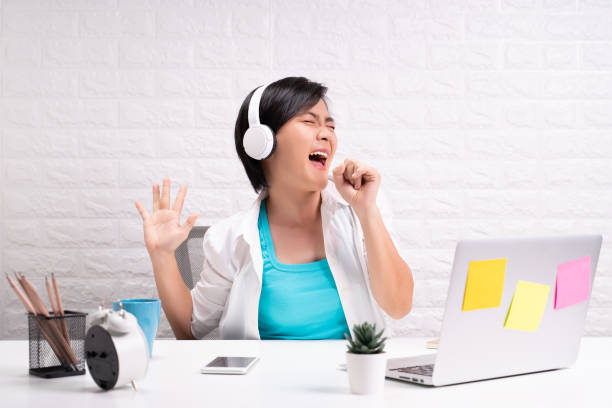 Happy woman with headphones listening music at office Happy woman with headphones listening music at office singing stock pictures, royalty-free photos & images