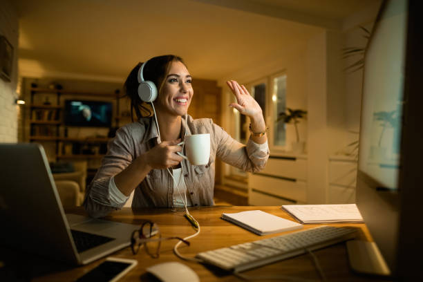 Happy woman with headphones making video call over computer at night. Happy woman drinking tea and waving to someone while having video call over desktop PC in the evening at home. video call stock pictures, royalty-free photos & images