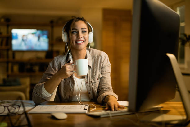 Happy woman with headphones surfing the net on desktop PC at night. stock photo