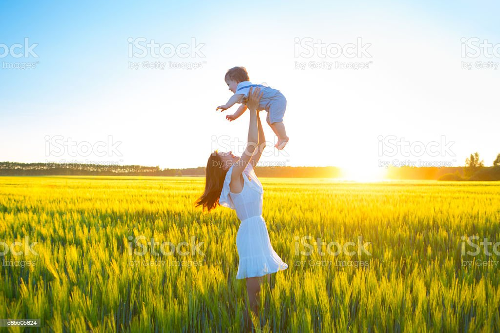 Happy woman with her baby boy on summer sunny day. stock photo