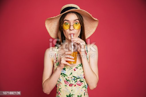 Portrair of happy and excited blond trendy woman in hat with fresh drink in hands isolated on pink background. Summer mood