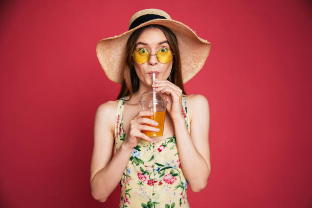Happy woman with juice in summer hat Portrair of happy and excited blond trendy woman in hat with fresh drink in hands isolated on pink background. Summer mood drinking straw stock pictures, royalty-free photos & images
