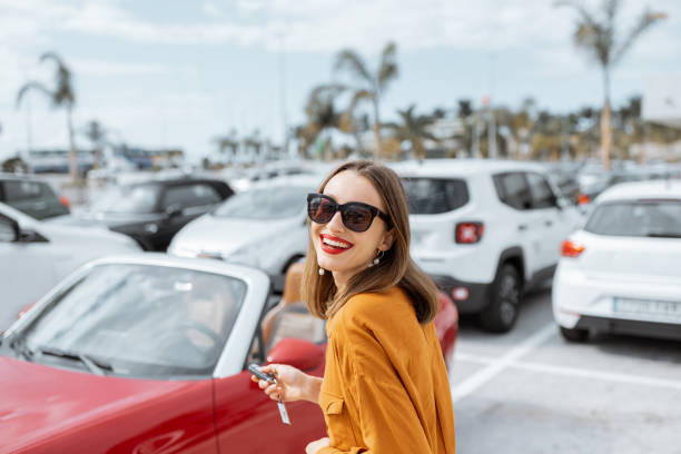 Happy woman with keys near the car at the parking stock photo