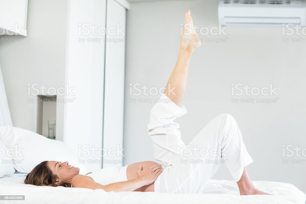 Happy woman with leg up on bed stock photo