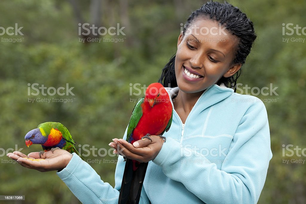 Happy woman with parrot in each hand. stock photo