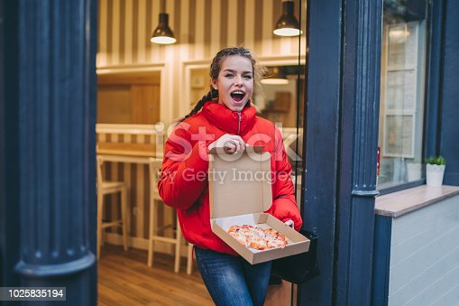 Excited woman showing freshly baked pizza