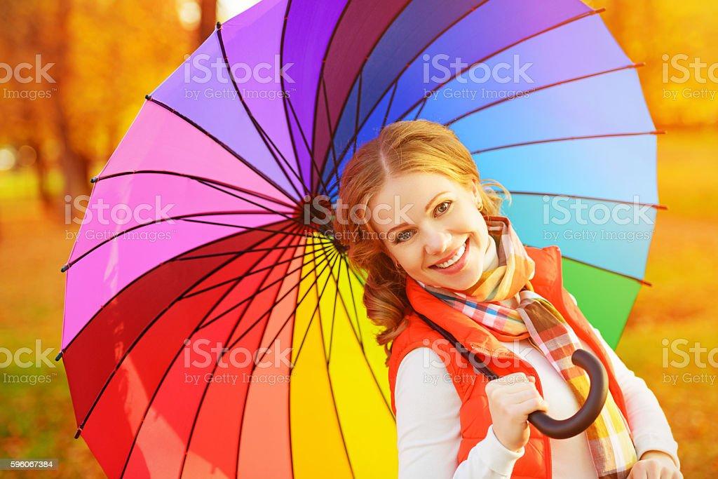 happy woman with rainbow multicolored umbrella under rain in par royalty-free stock photo