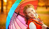 istock happy woman with rainbow multicolored umbrella under rain 516068626