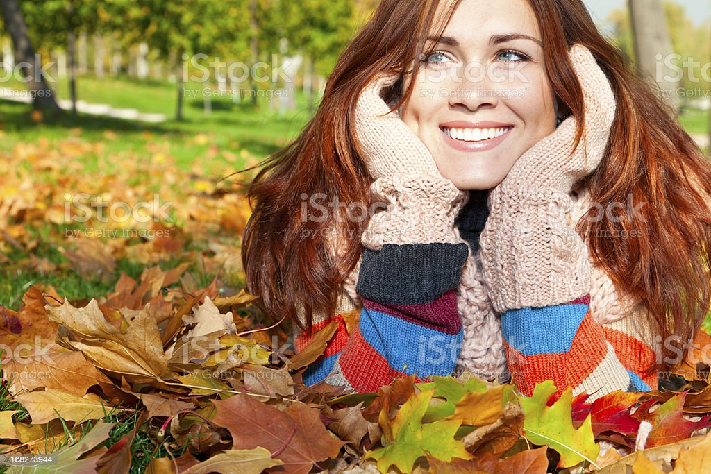 Happy woman with red hair laying on the autumn leaves royalty-free stock photo