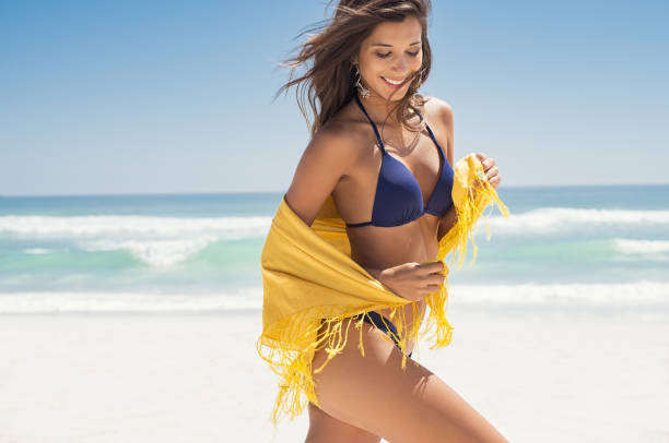 Happy woman with scarf at beach stock photo