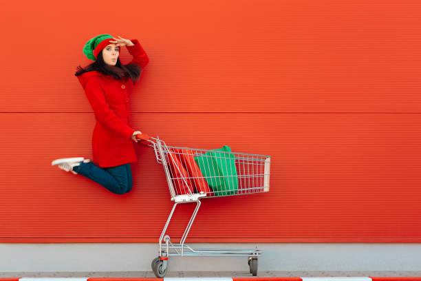 glückliche frau mit shopping cart ready for christmas sale - günstige weihnachtsgeschenke stock-fotos und bilder