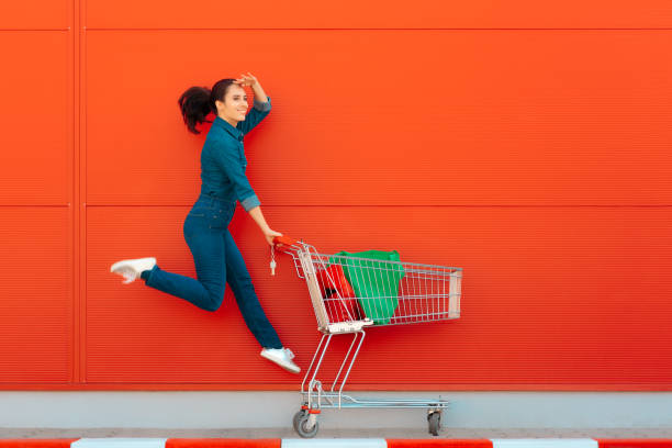 Happy Woman with Shopping Jumping with Joy Excited supermarket customer on sale season cart stock pictures, royalty-free photos & images