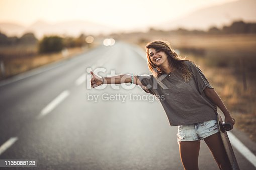 Happy woman hitchhiking on the road while holding her skateboard and looking at camera. Copy space.