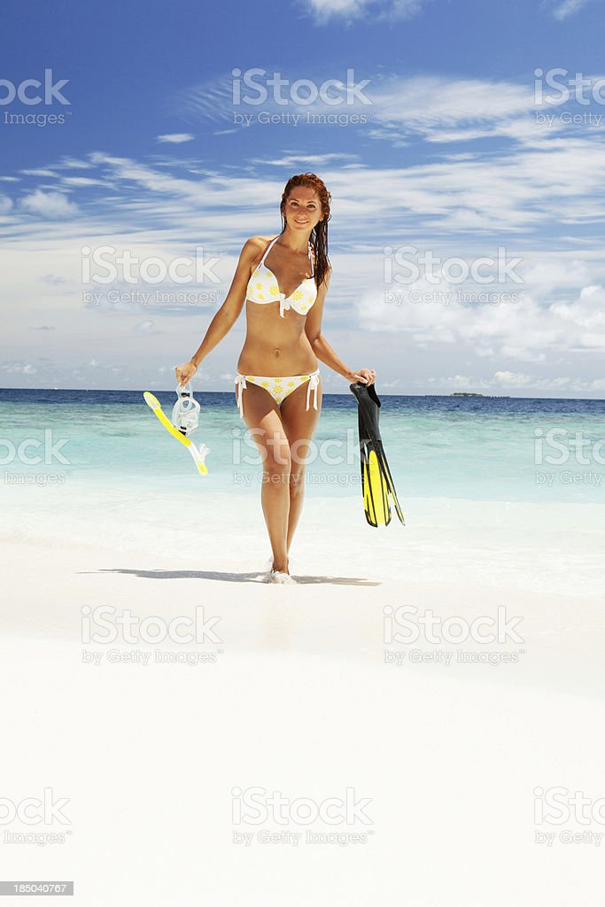 Happy woman with snorkeling equipment on the beach stock photo