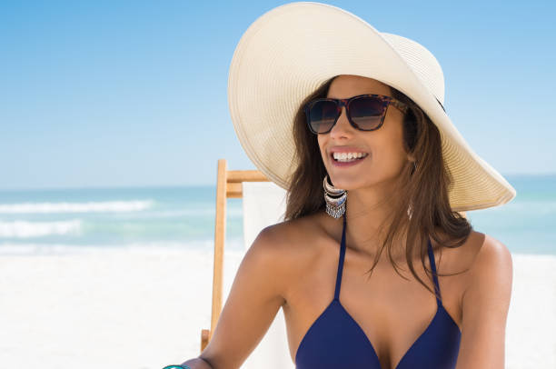 Happy woman with straw hat at beach stock photo