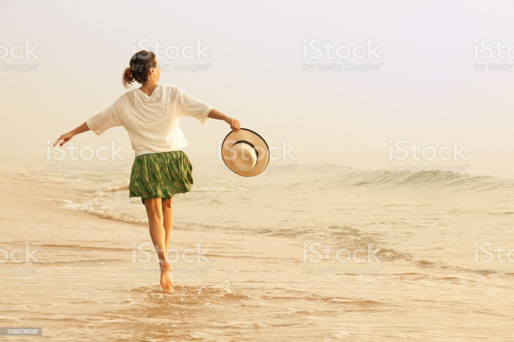 Happy woman with straw hut dancing on beach stock photo