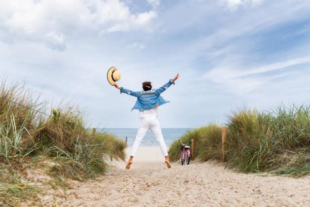 Glückliche Frau mit Strohhütte am Strand – Foto