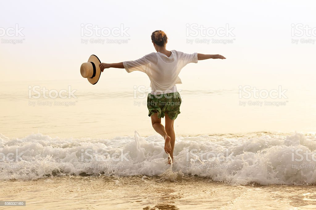 Happy woman with straw hut on beach stock photo
