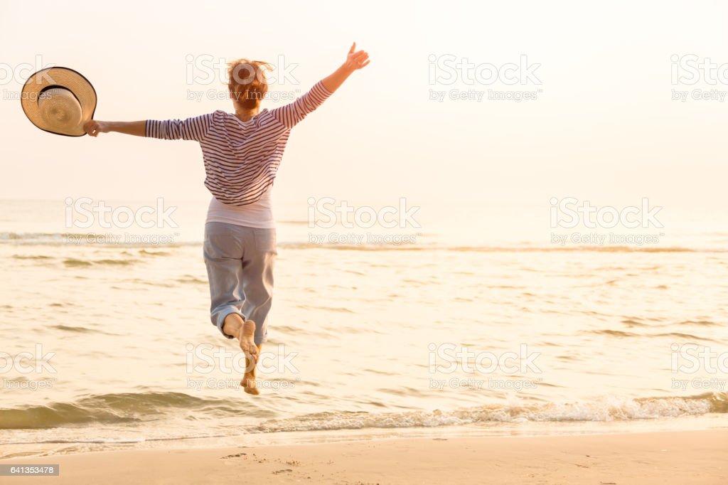 Donna felice con capanna di paglia sulla spiaggia - foto stock