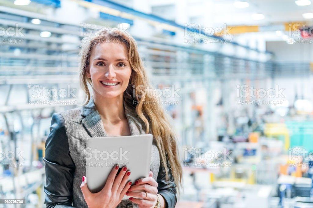 Glückliche Frau mit Tablet in Kunststoff-Fabrik – Foto